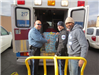 Police Officer and two other volunteers putting a box of toys into an ambulance