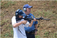 Officer standing beside young man shooting a rifle