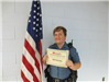 Officer standing beside American flag holding certificate