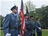 Four officers in a line in dress uniform carrying flags