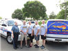 Five officers standing in front of a truck with torch Run sign on it