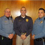 Three officers standing in a line smiling into camera