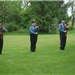 Three officers in uniform standing at attention with  rifles in hand in grass