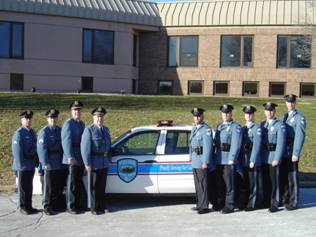 Image of nine officers standing in front of a patrol car in parking lot