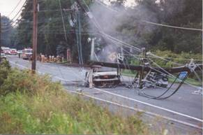 image from afar of a white pickup truck crushed by a telephone pole