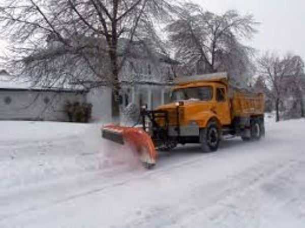 Large snow plow machine running through the streets clearing the snow after a storm