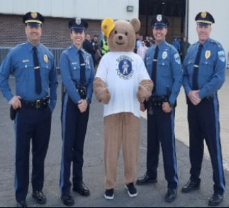 Police officers standing with bear mascot